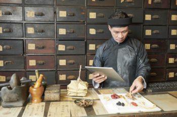 Chinesischer Mediziner bei der Zusammenstellung von Heilkräutern