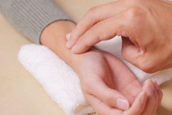 Hände von Patient und Mediziner zur Pulsdiagnose